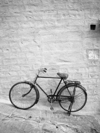 Photo pour Vieux vélo se penche contre un mur de briques bleu vif - image libre de droit