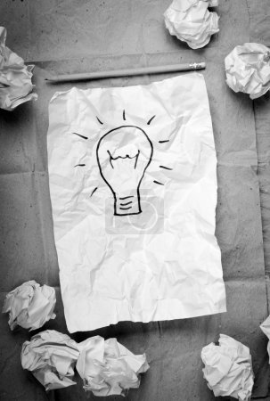 Photo for Crumpled paper with a lightbulb idea concept and crumpled paper attempts around it - Royalty Free Image