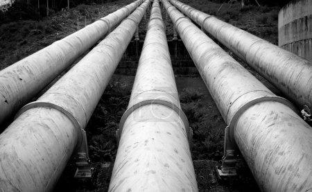 Photo pour Des oléoducs hydroélectriques massifs convergent vers une colline - image libre de droit
