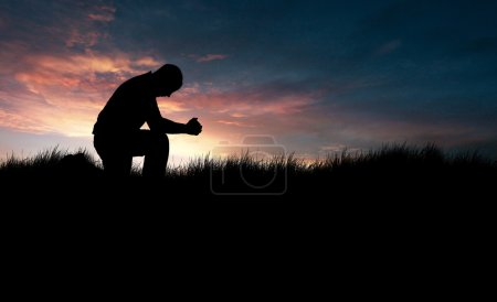 Photo for Man praying in the grassy field - Royalty Free Image