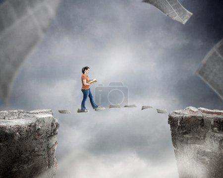 Photo pour Femme lisant un livre et marchant sur des pages au-dessus d'une falaise . - image libre de droit