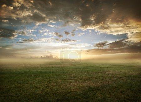 Photo pour Beau coucher de soleil avec des nuages spectaculaires sur un champ herbeux - image libre de droit