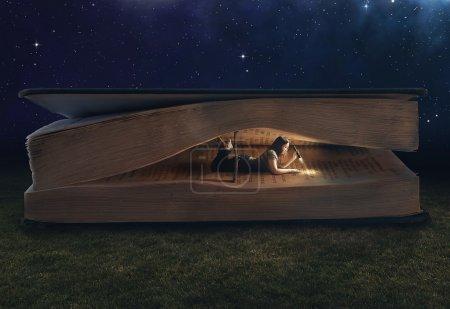 Photo pour Femme lisant à l'intérieur d'un grand livre - image libre de droit