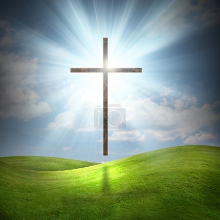 Photo for Large christian cross with sun rays over grassy field. - Royalty Free Image