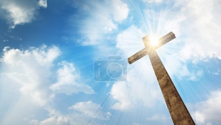 A wooden Christian cross with bright sun and cloud...