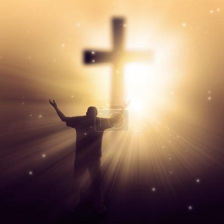 Photo pour Un homme marchant vers une croix avec des rayons de soleil - image libre de droit