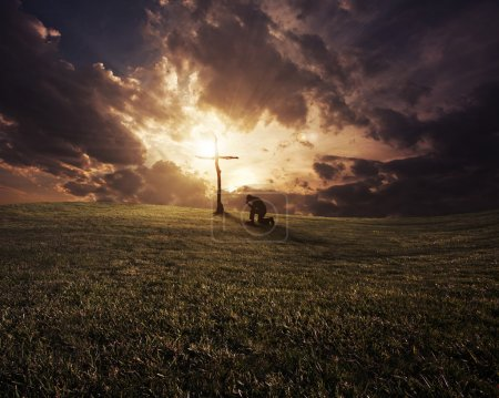 Photo for A man kneeling at a cross at sunset. - Royalty Free Image