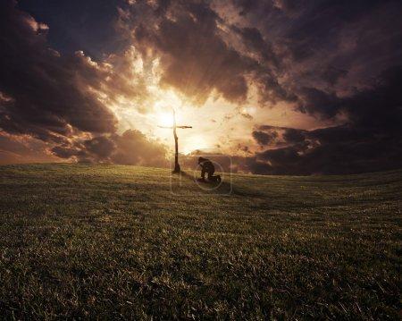 Photo pour Un homme agenouillé à une croix au coucher du soleil . - image libre de droit