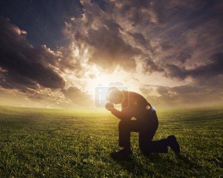 Photo pour Silhouette homme priant au coucher du soleil - image libre de droit