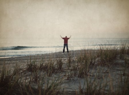 Photo for Man stands with his hands raised up against the sea and clouds - Royalty Free Image
