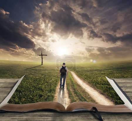 Photo for Man walking on a Bible towards a cross - Royalty Free Image