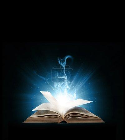 Foto de Libro brillante con luces azules en fondo negro. - Imagen libre de derechos