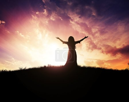 Photo pour Femme levant les mains au coucher du soleil - image libre de droit
