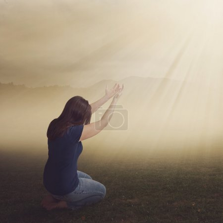Photo for A woman on her knees in worship in a field. - Royalty Free Image