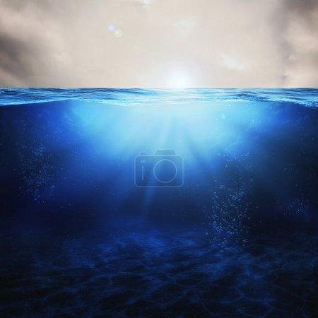Photo pour Sous les vagues dans l'eau bleue avec les rayons du soleil . - image libre de droit