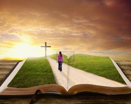 Photo pour Une femme marche le long d'une route sur un livre vers la croix . - image libre de droit