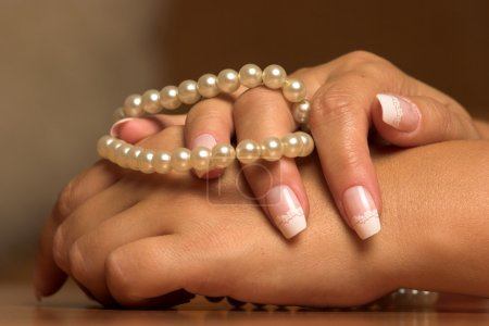 Hand with a pearl necklace touching....