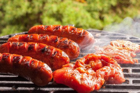 Grilling sausages on barbecue grill. Selective foc...