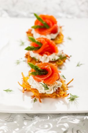 Photo for Potato pancakes topped with smoked salmon,asparagus and sour cream for holiday - Royalty Free Image