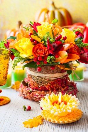 Photo pour Table de fête avec panier de fleurs d'automne, bougie et citrouille - image libre de droit