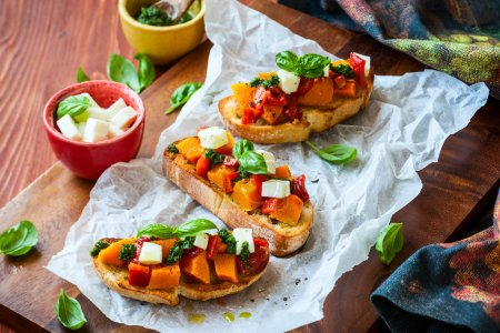Photo for Bruschetta with roasted pumpkin, red pepper,pesto and cheese - Royalty Free Image