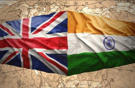 Photo pour Agitant des drapeaux britanniques et Indiens sur le fond de la carte politique du monde - image libre de droit