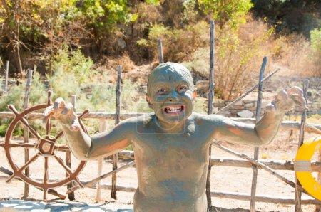 Boy grimaces in mud bath