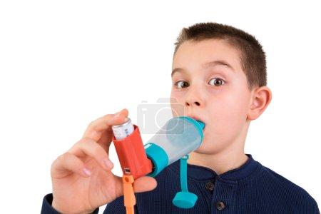 Foto de Nueve años chico con asma alérgica, inhalando su medicación espaciador mientras mirando con su amplia abrió los ojos quizás él está recibiendo energía impulso - Imagen libre de derechos