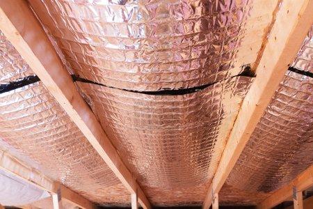 Photo pour Isolation des combles avec barrière froid en fibre de verre et barrière réfléchissante de chaleur utilisé comme écran acoustique entre les solives du grenier pour augmenter la ventilation pour réduire l'humidification - image libre de droit