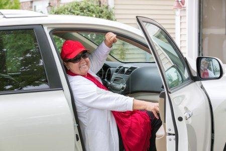 Photo pour Senior Dame avec chapeau rouge, assis sur le siège passager se prépare, fermer la porte et prendre la route, elle a le sourire sincère sur son visage - image libre de droit