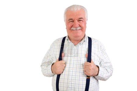 Confident senior man holding his suspenders