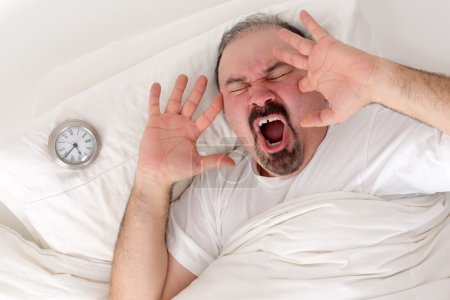 Man yawning loudly resting in bed