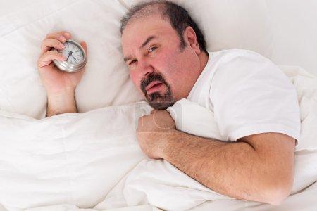 Foto de Hombre irascible mirando tristemente la cámara mientras yace en la cama con el reloj de alarma en su mano después de una noche de insomnio querer permanecer en la cama hasta el mediodía - Imagen libre de derechos