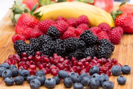 Photo for Assorted freshly washed fruit in the kitchen arranged on a wooden countertop in colourful rows with blueberries, blackberries, pomegranate seeds, raspberries, strawberries and a fresh banana - Royalty Free Image