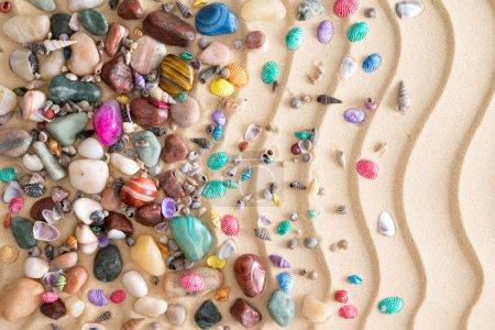 Pebbles, gemstones and shells on beach sand