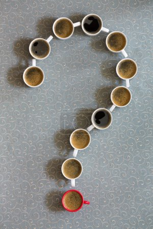 Photo for White coffee mugs filled with milky freshly brewed coffee arranged as a question mark with a single red cup as the point on a grey background in a conceptual image, viewed from above - Royalty Free Image