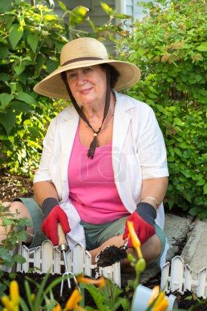 Senior woman planting flowers in the garden