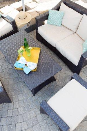 Photo pour Vue d'en haut sur un patio extérieur haut de gamme vacant avec salon de jardin moderne avec coussins rembourrés confortables sur pavage avec une table centrale avec un plateau de boissons réfrigérées - image libre de droit
