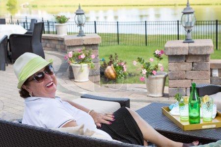 Senior woman enjoying a drink on the terrace