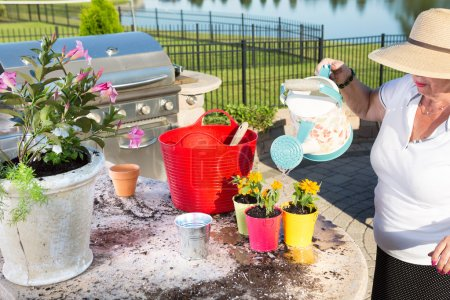 Senior lady watering newly potted plants