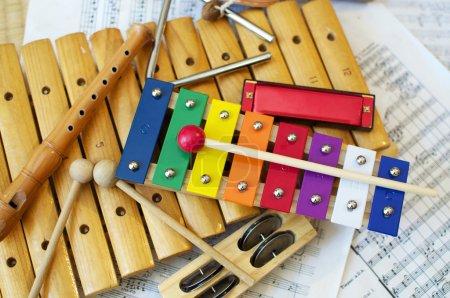 Photo pour Certains instruments de musique typiques et colorés utilisés principalement par les enfants. La partition musicale en arrière-plan est dans le domaine public . - image libre de droit