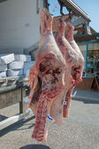Fresh meat hanging being delivered.