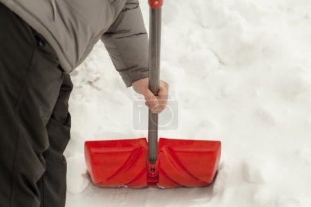 Man with a snow shovel near the snow pile