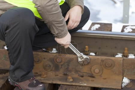 Railroad worker with wrench on the railway bridge fix the nut