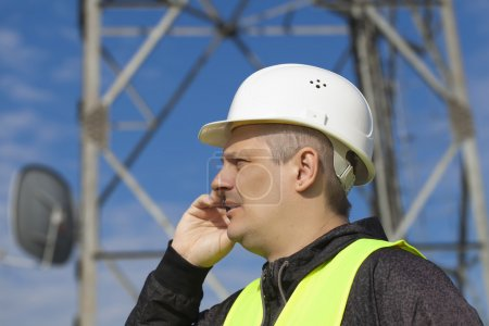 Engineer talking on the cell phone near to gsm tower