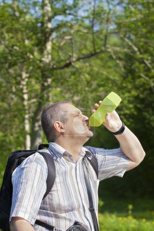 Foto de Excursionista beber agua de botella en los senderos del bosque - Imagen libre de derechos