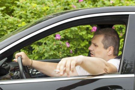 pilote avec une cigarette à la main en voiture