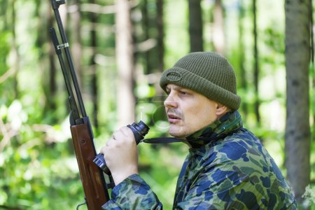 Man with optical rifle and binoculars in the woods