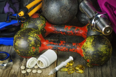 Dumbbells, sports gear with pills and medicines