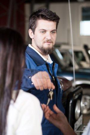 Handsome car mechanic at work